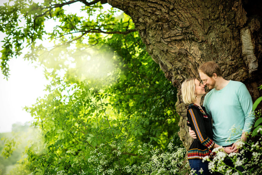 couple kissing under back tree