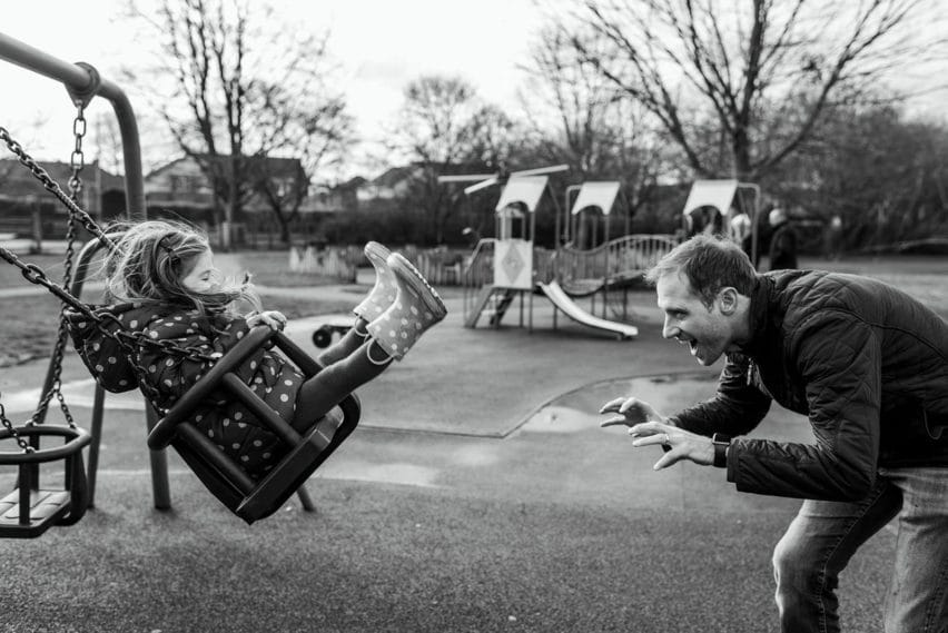 Father and daughter at park on swings