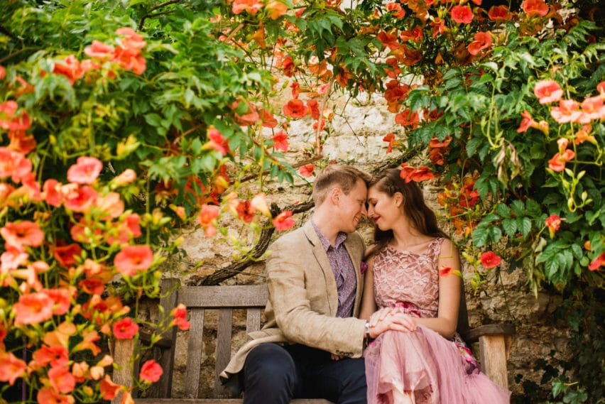 couple sitting under roses on bench