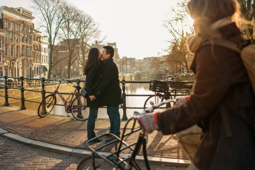 Couple kissing on bridge in Amsterdam