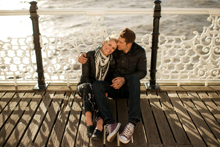 couple sitting on pier in Brighton