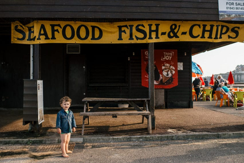 Little boy at beach under fish and chip shop sign