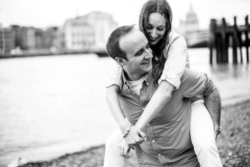 girl on back of boyfriend along the banks of London