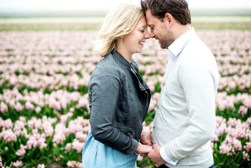 couple with heads together in tulip field