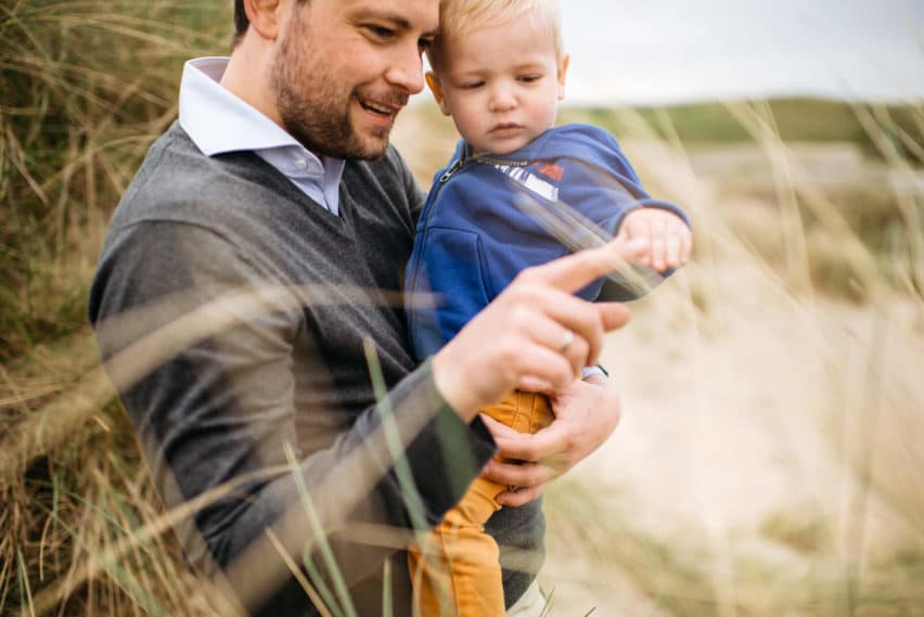 father and son in sand dunes at the beach
