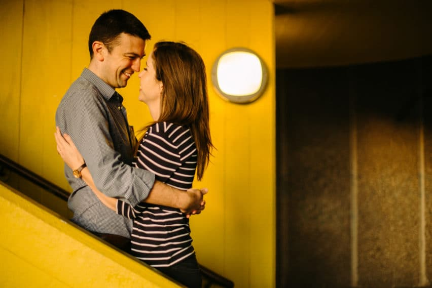 yellow backdrop with couple on stairs