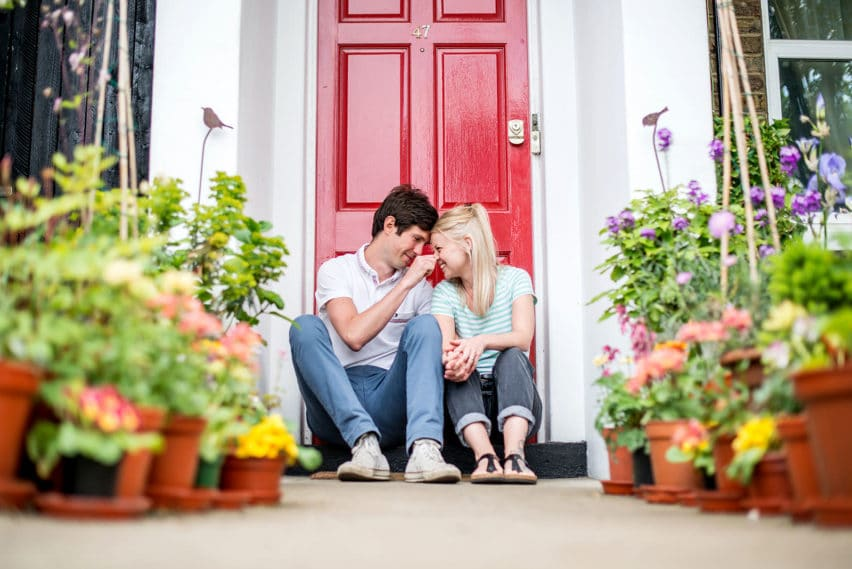 couple sitting on doorstop of their new home