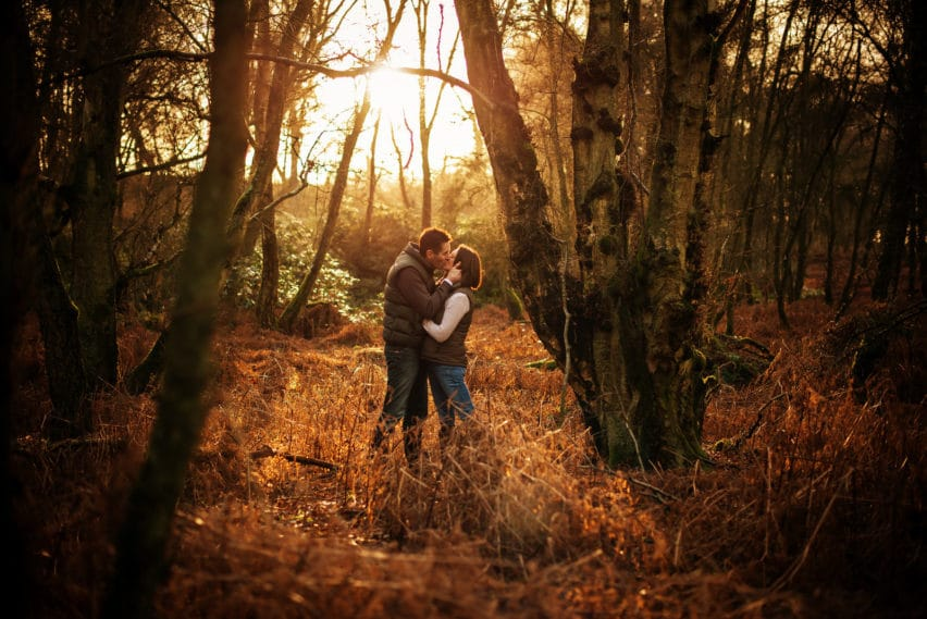 couple kiss in winter woodland