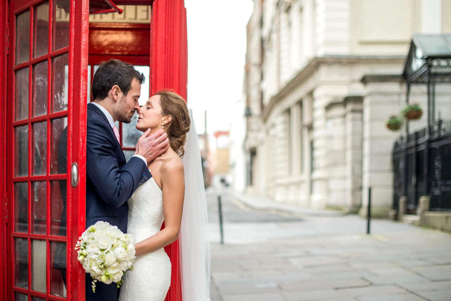 bride and groom wedding portrait by red telephone box