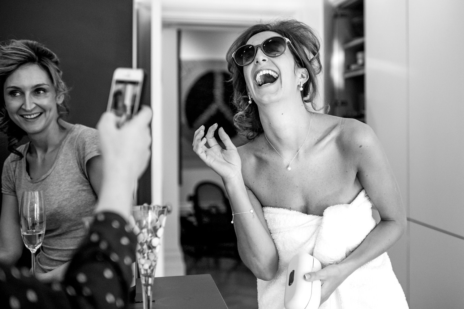 bride in towel laughing with sunglasses on