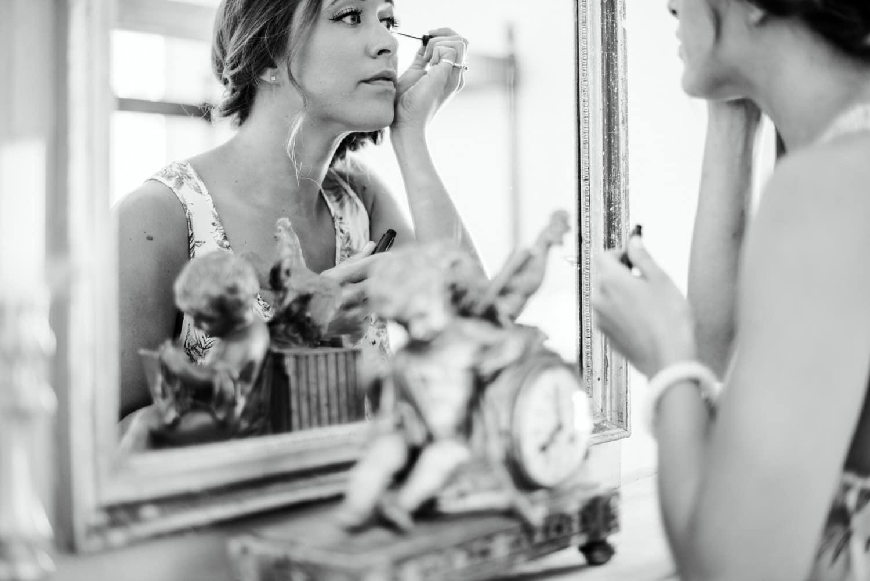 bridesmaid applying make up in mirror of Chateau de Lacoste wedding venue