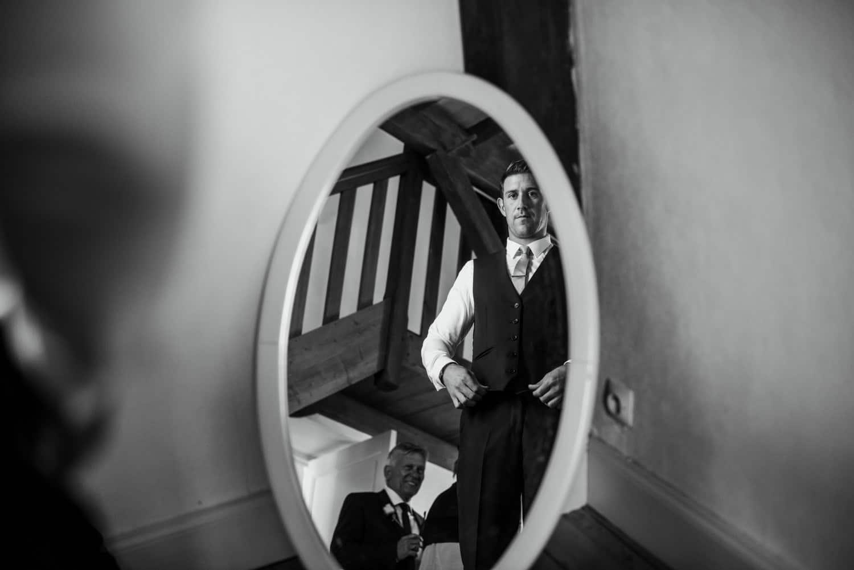 groom in reflection of mirror at Chateau de Lacoste wedding venue