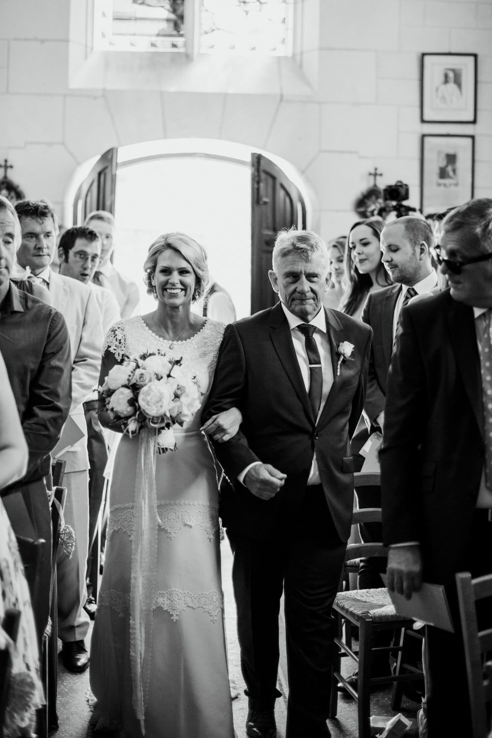 bride walking down the aisle in the chapel at Chateau de Lacoste wedding venue in France