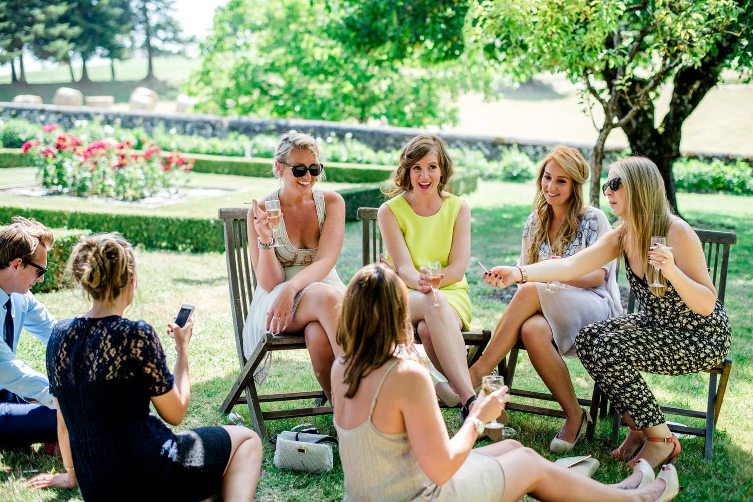 guests sitting in the gardens of Chateau de Lacoste wedding venue
