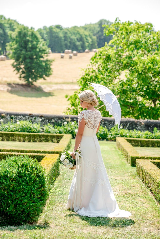portrait of bride with parasol in gardens of Chateau de Lacoste wedding venue