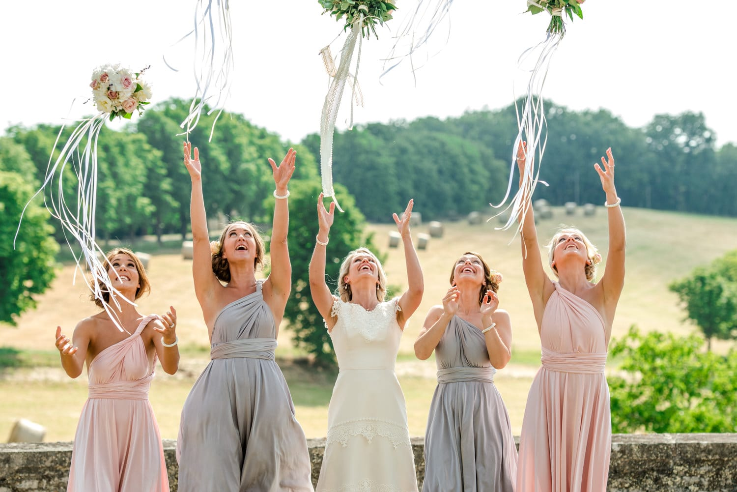 bride and bridesmaids throwing their bouquets at Chateau de Lacoste wedding venue