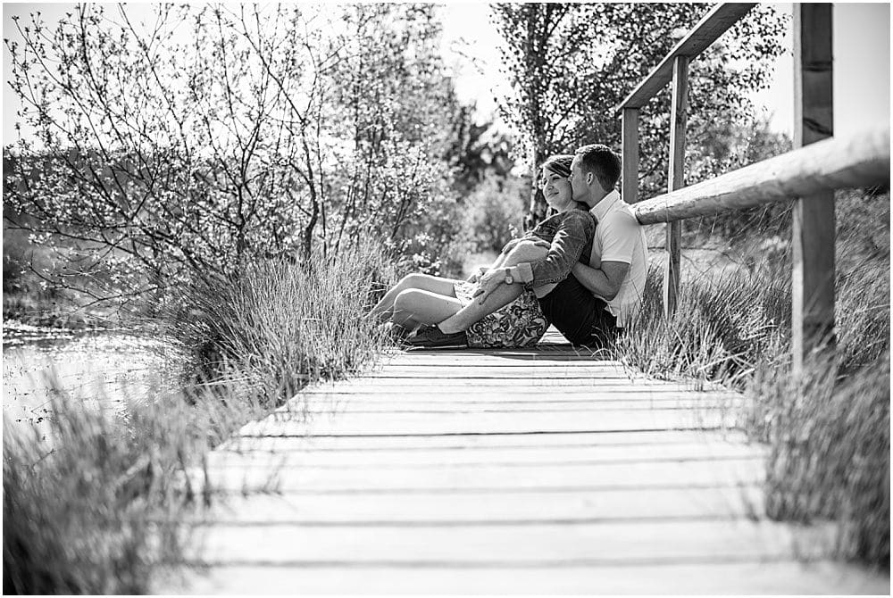 Couple sitting on deck during engagement session