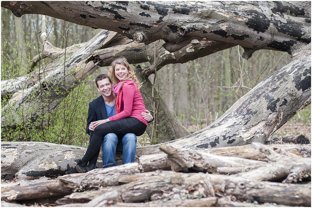Couple sitting on fallen tree during engagement session