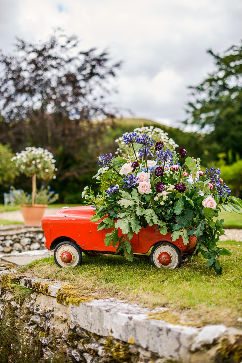 old red tin car with floral display