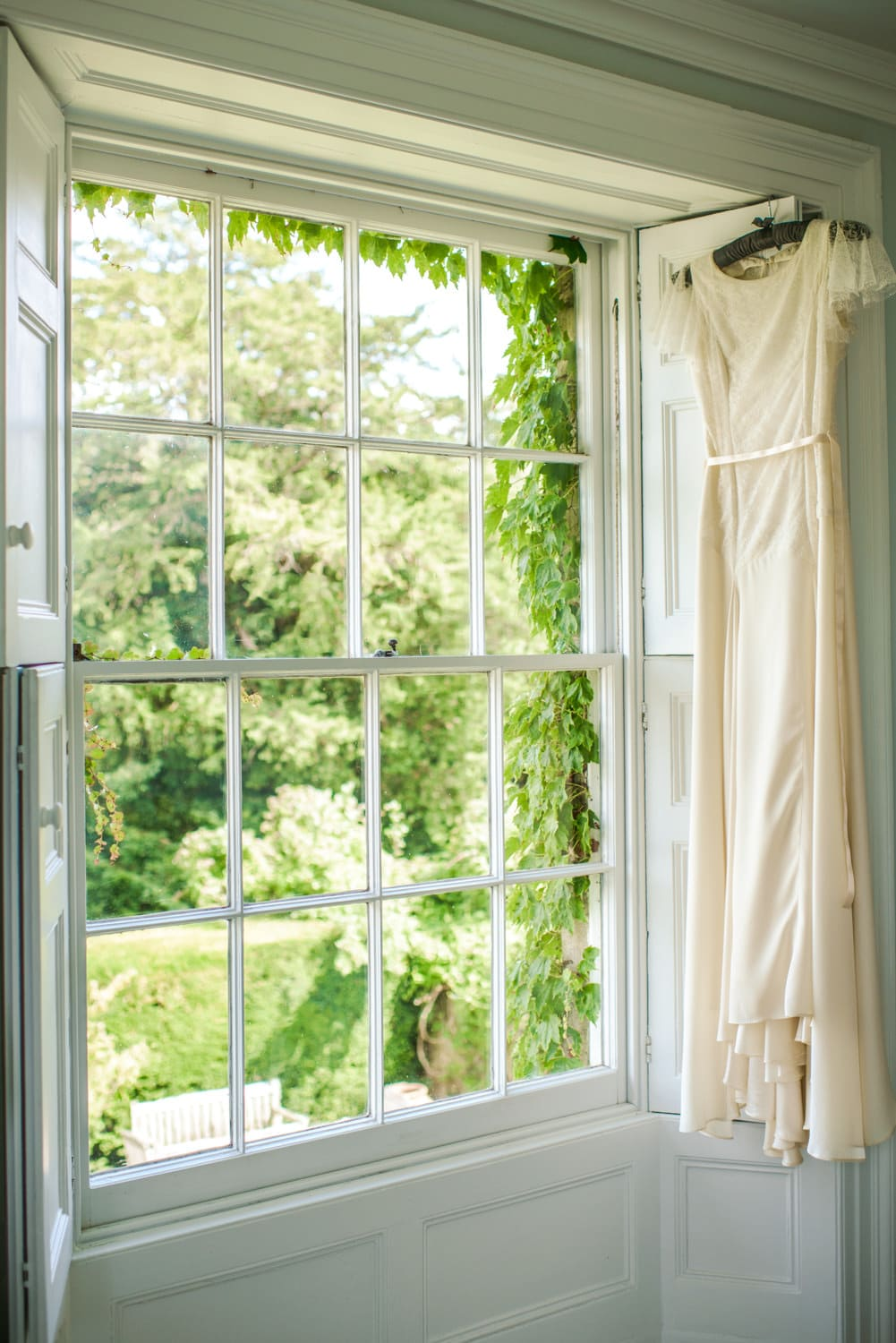 wedding dress hanging next to sash windows