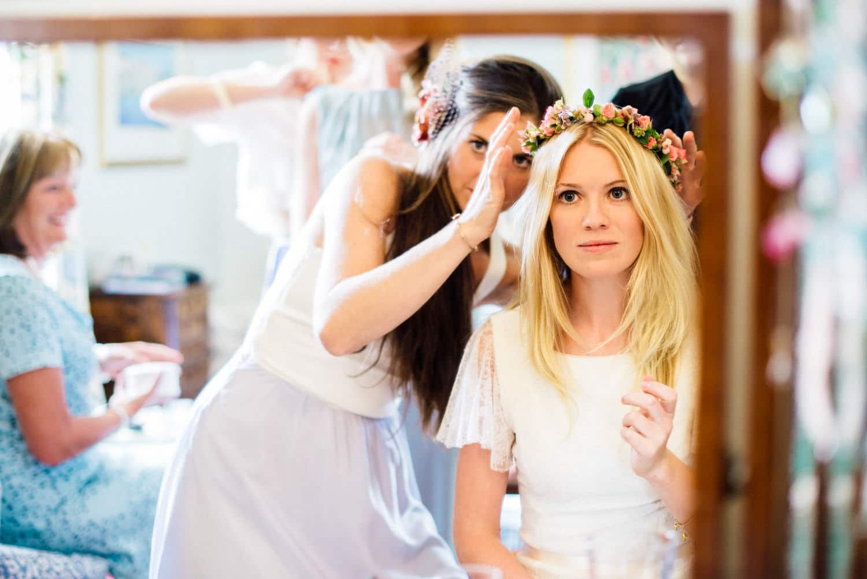 bride looking in mirror with flower crown