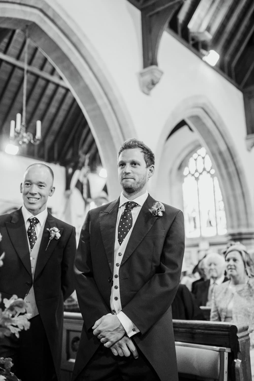 groom waiting for bride to walk down the aisle in church