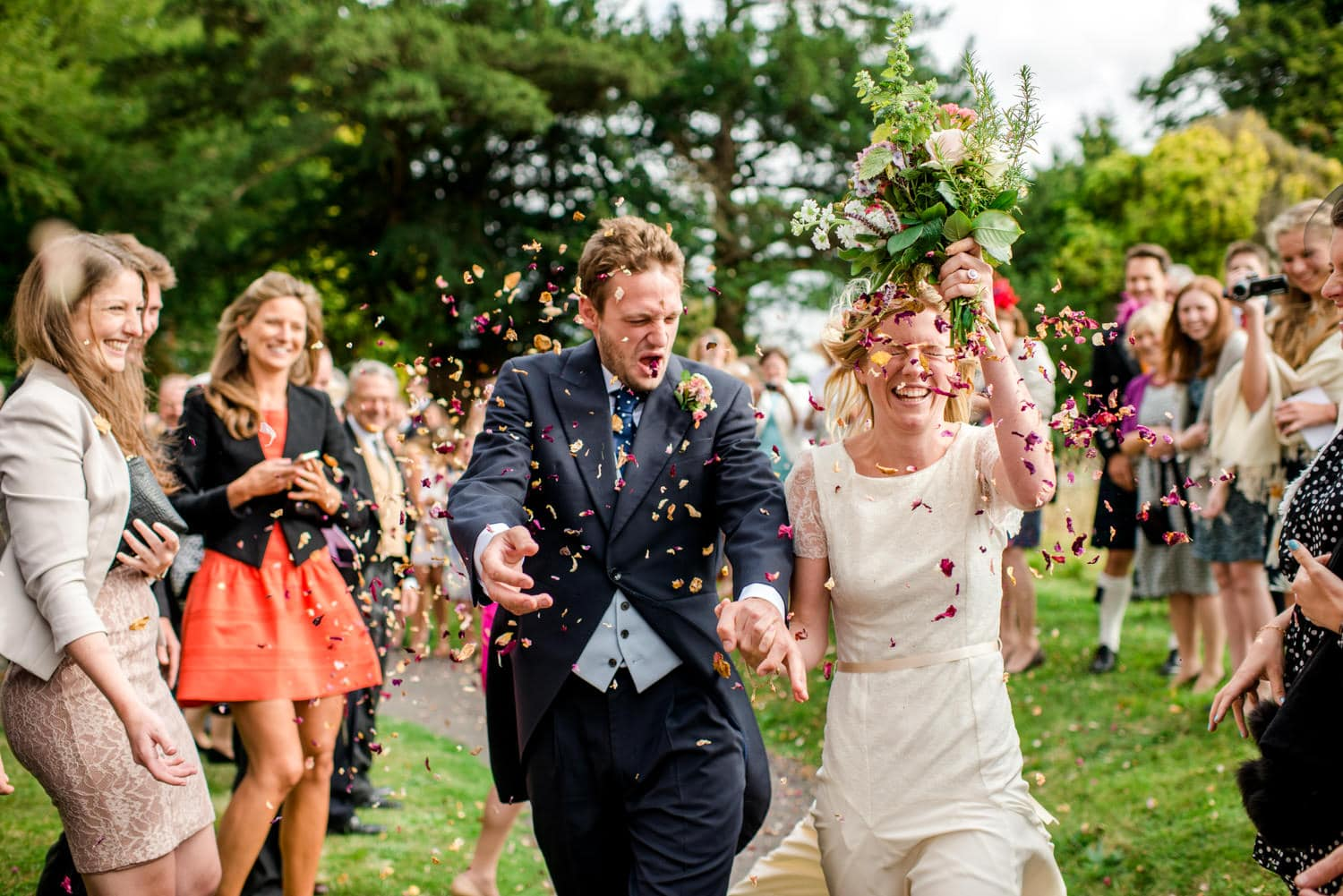 bride and groom walking through confetti at Dorset country wedding
