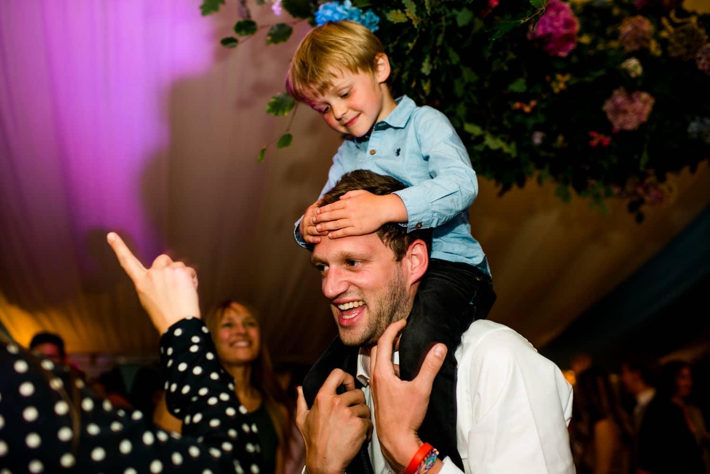kid on shoulders of groom during wedding party