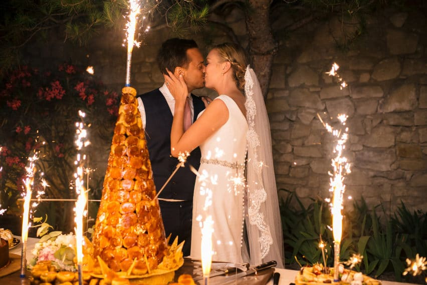 bride and groom kiss in front of cake and sparklers