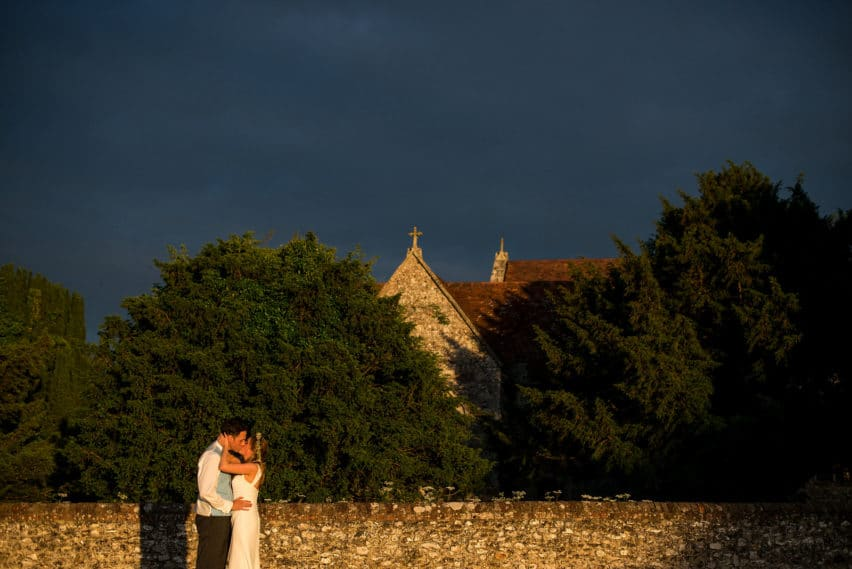 dramatic skies above church and bride and groom hugging