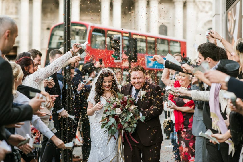 couple walking through confetti with London red bus behind
