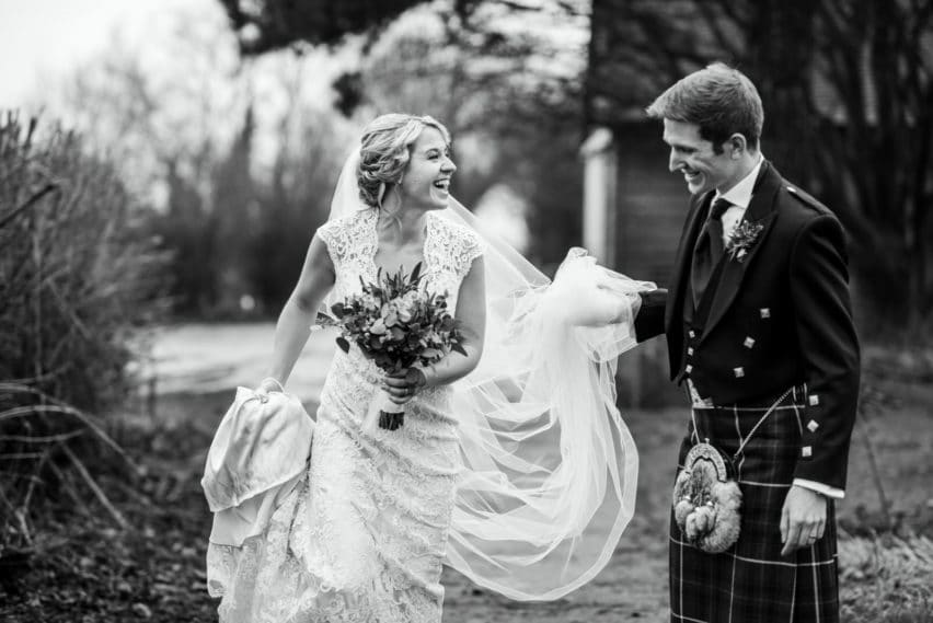 groom in kilt holding up brides dress so it doesn't get dirty