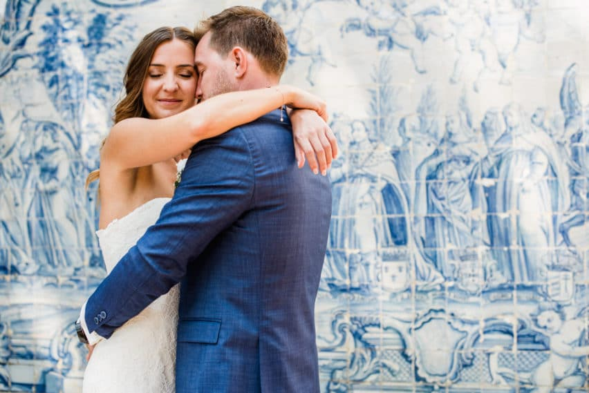 bride and groom embrace in front of traditional Portuguese tiles