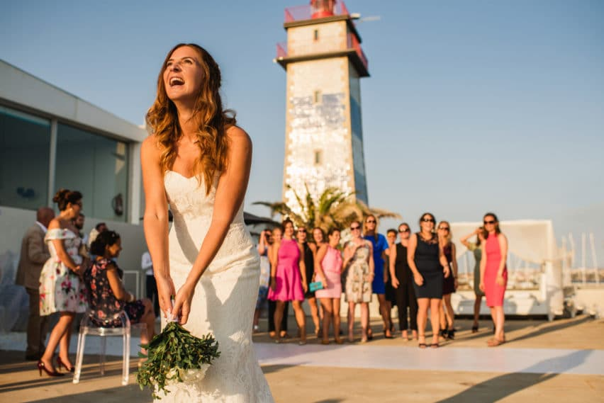 bride throwing bouquet by a lighthouse