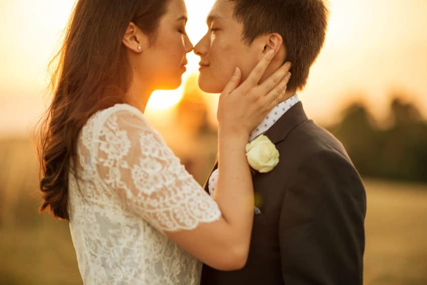 bride and groom at sunset kissing