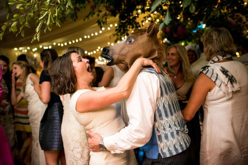 wedding guest wearing horse head on dance floor