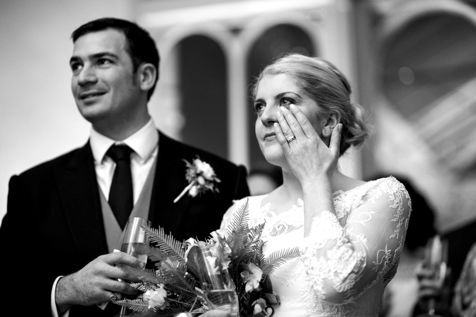 bride wiping tear away during speeches