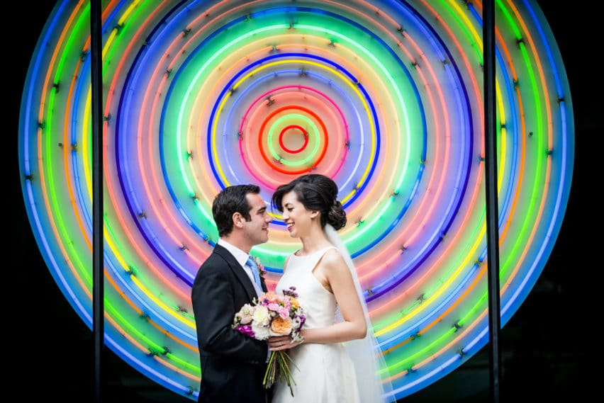 bride and groom portrait in front of neon sign