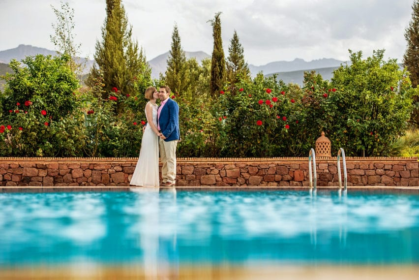Bride and groom portrait by pool in Morocco