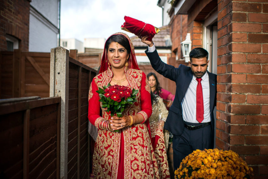 muslim wedding traditions, bride leaving house under the koran