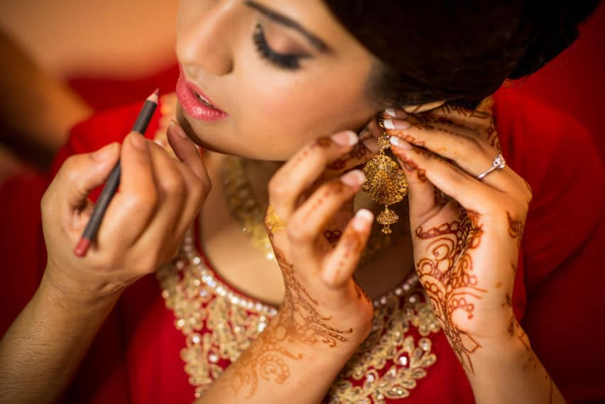 bride in red Indian dress putting earring on