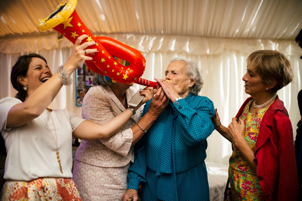 Grandma blowing an inflatable saxophone