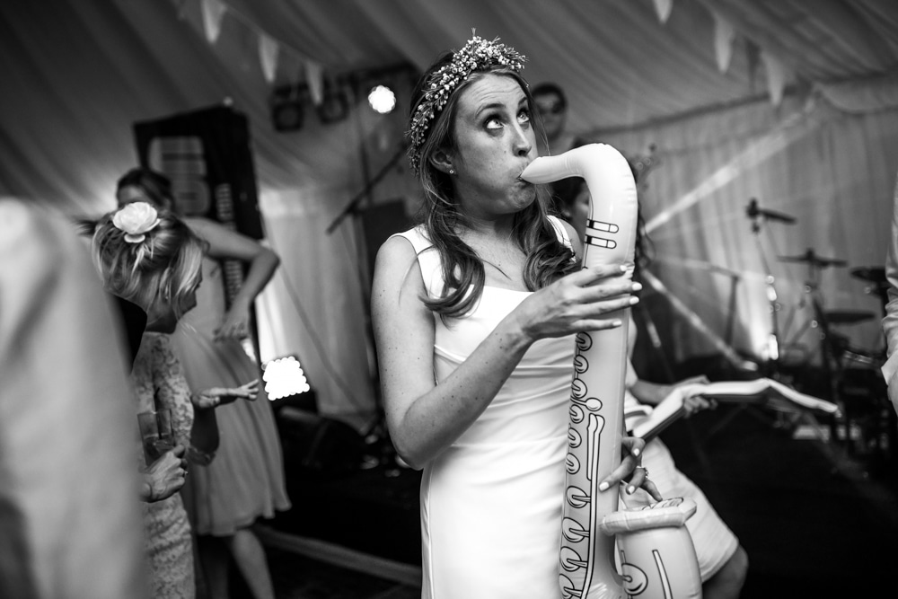 Bride blowing inflatable saxophone