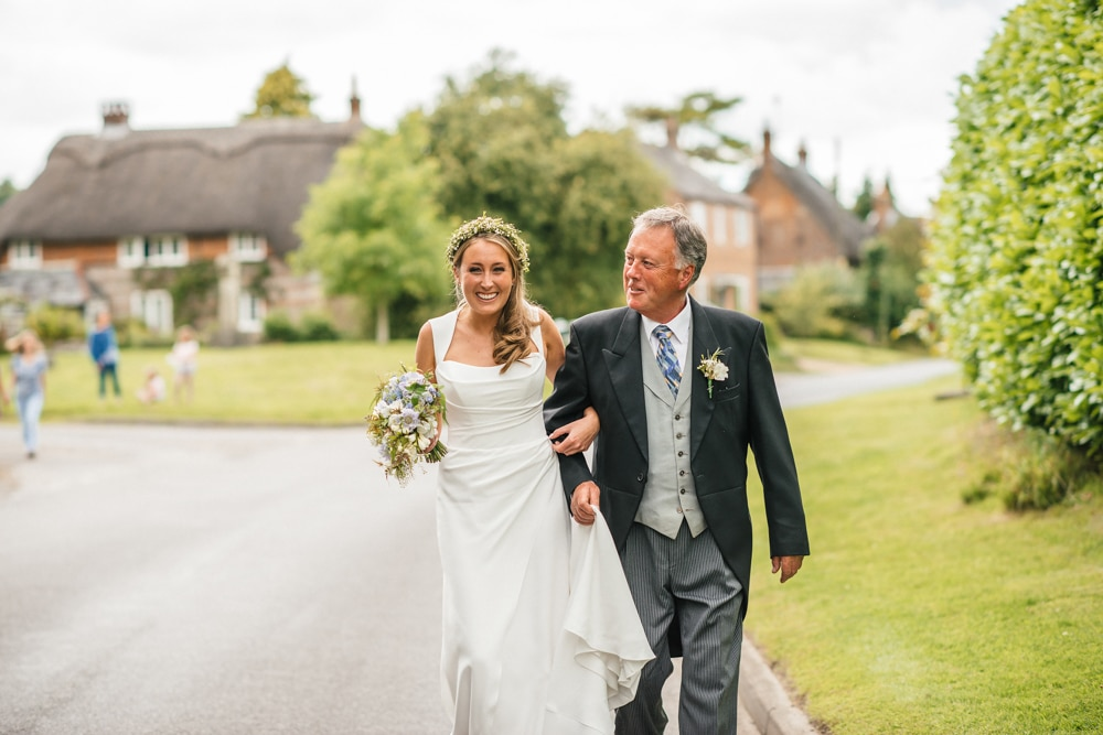 father of the bride walking his daughter to the church through village