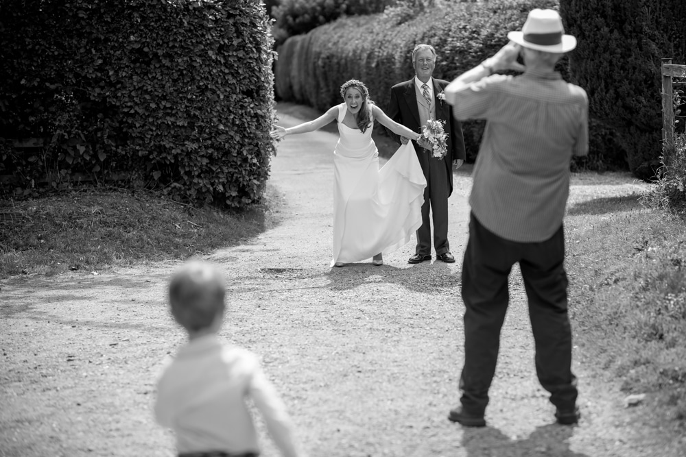 Bride welcoming page boy with open arms