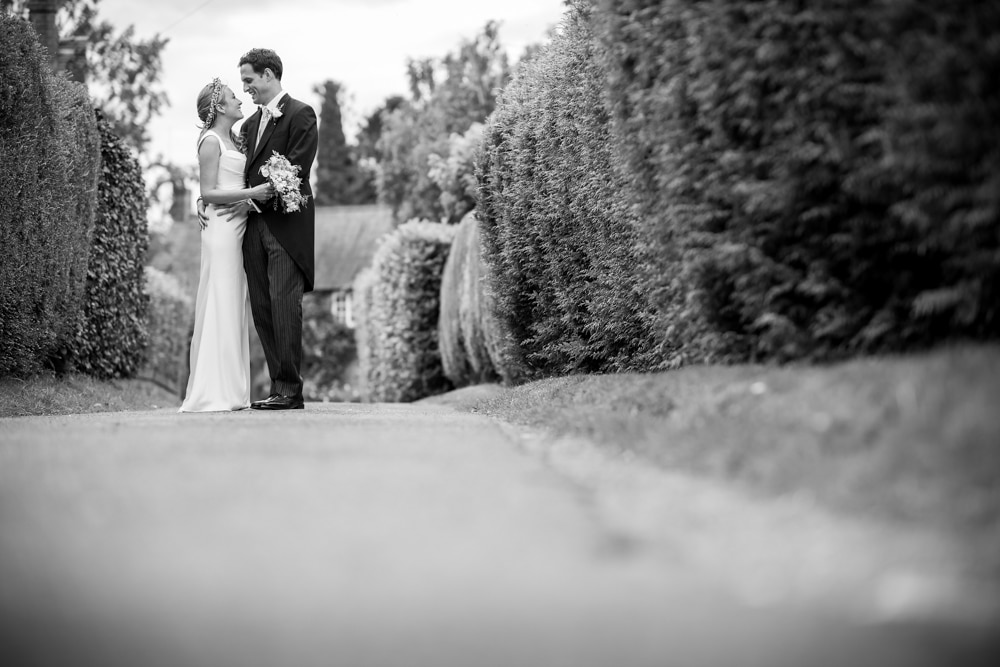 black and white portrait of bride and groom on path