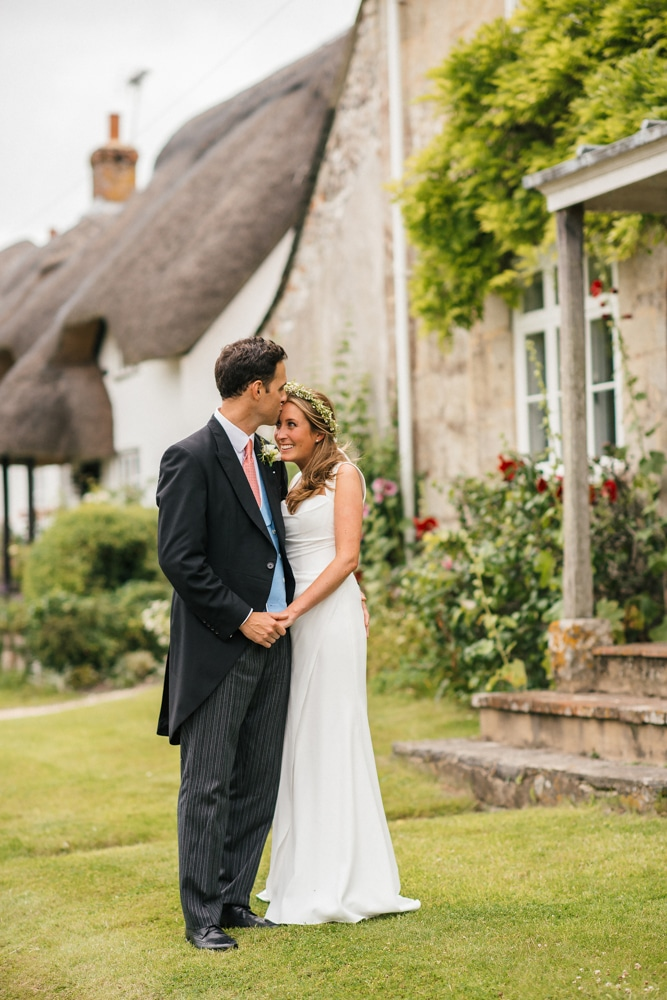 New Forest photography, bride and groom in village with thatched houses