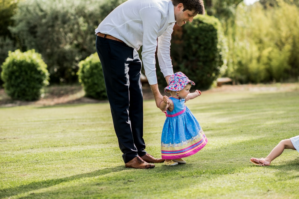 baby taking small steps with father