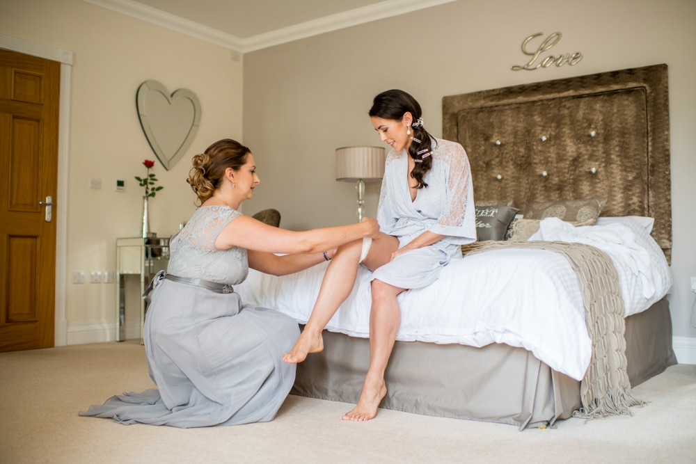 bridesmaid helping bride put garter on