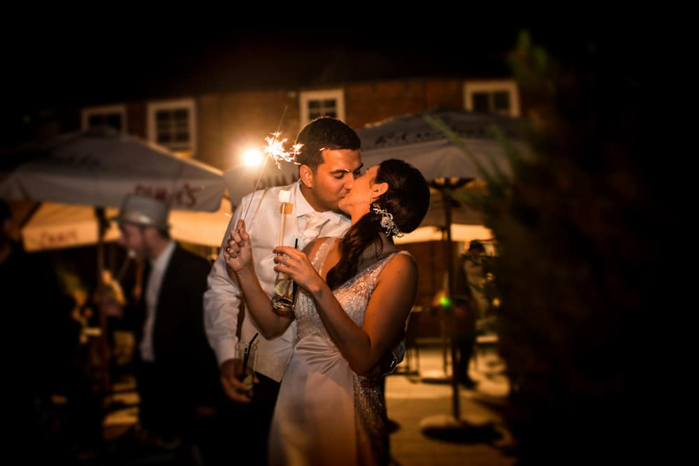bride and groom kissing with sparkler